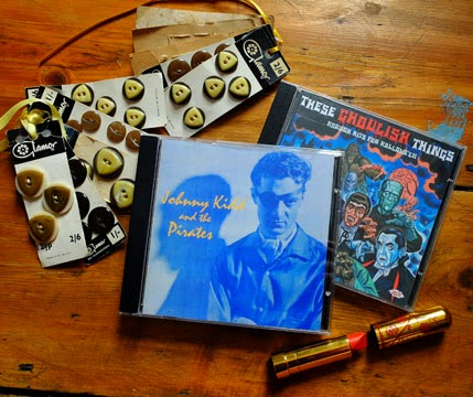 Some vintage buttons, two rock and roll CDs, and a Besame lipstick