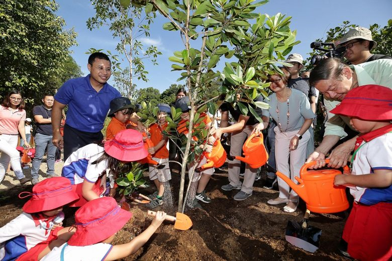 Second Minister for National Development Desmond Lee (in blue) joining around 50 pre-schoolers at a tree planting ceremony during the opening of the Nature Playgarden at HortPark yesterday.