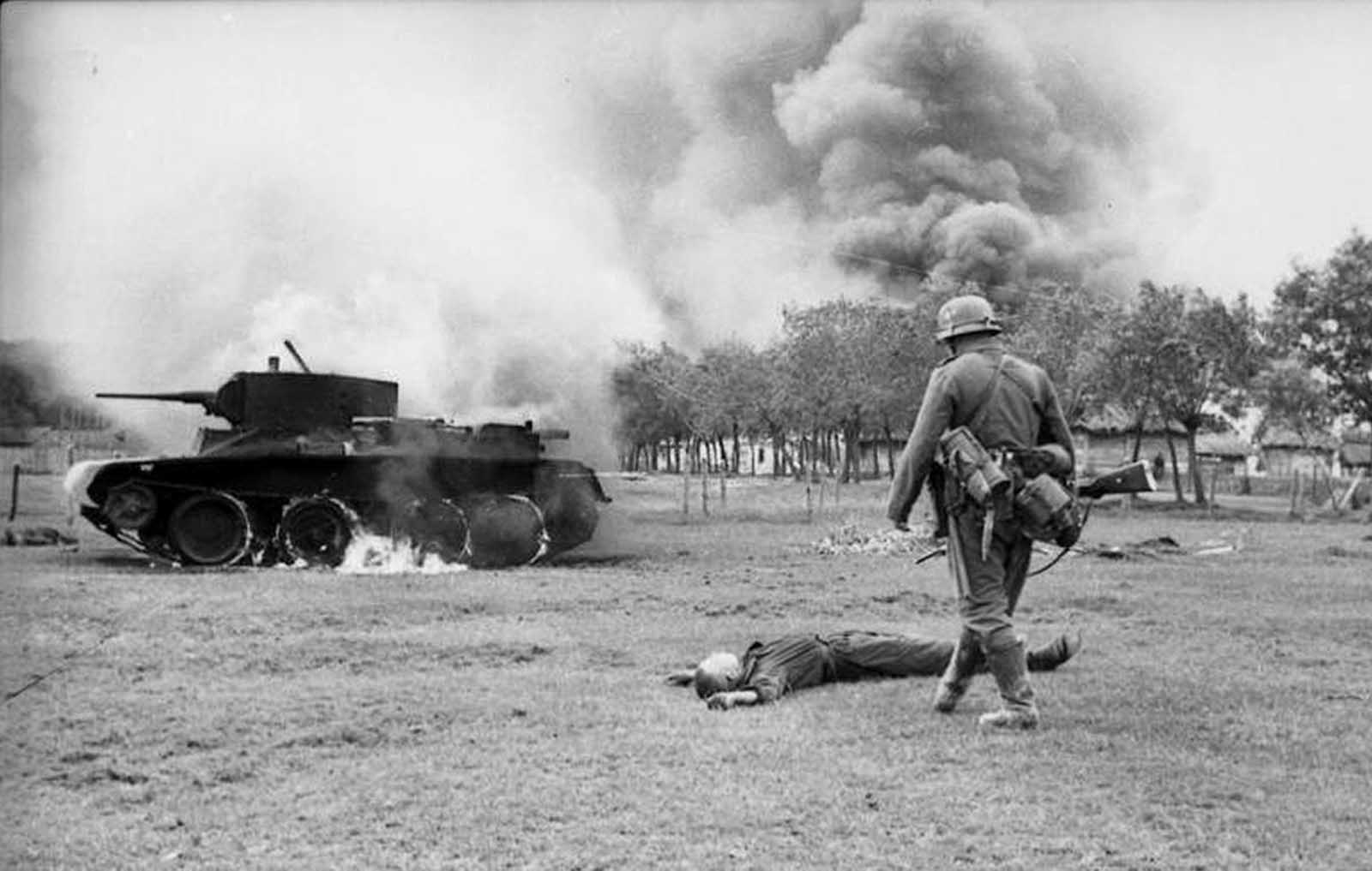 A German infantryman walks toward the body of a killed Soviet soldier and a burning BT-7 light tank in the southern Soviet Union in in 1941, during the early days of Operation Barbarossa.