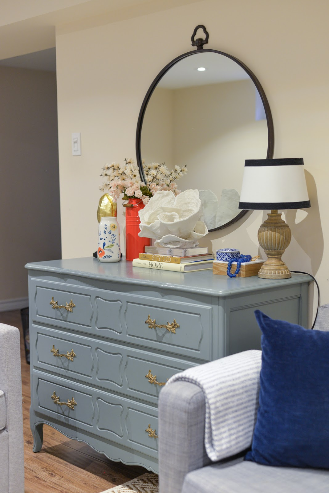 basement update, budget basement makeover, basement living room, coastal vignette, teal dresser, large round mirror over dresser