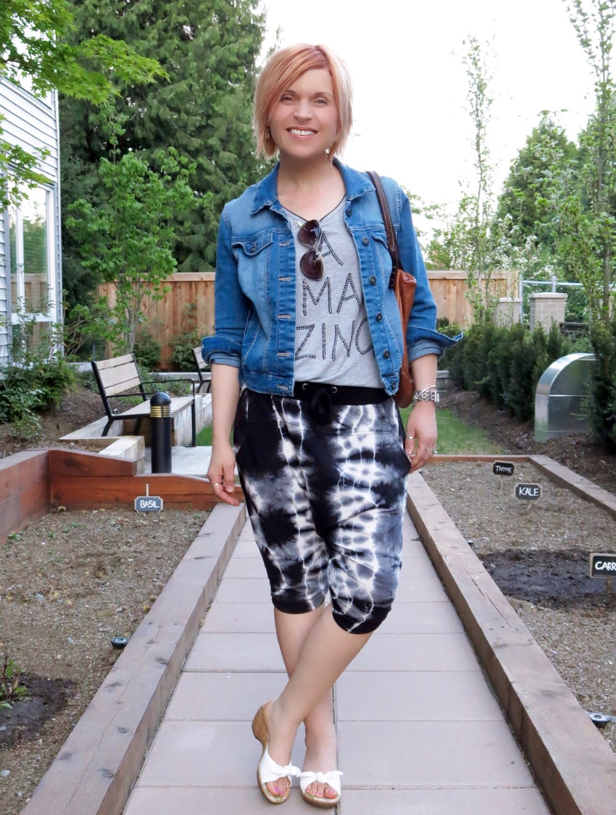 styling harem shorts with a graphic tee, denim jacket, and cork-soled slides