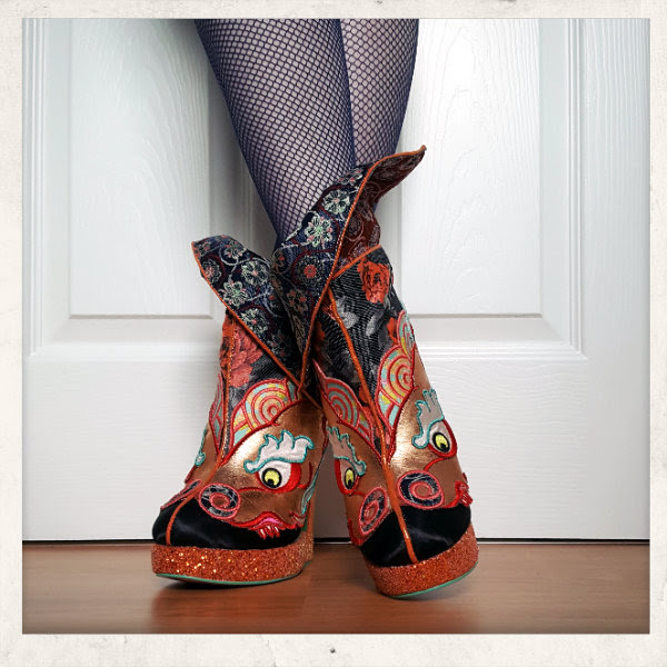 wearing Irregular Choice Tatsu ankle boots with crossed legs and cuff worn half up half down