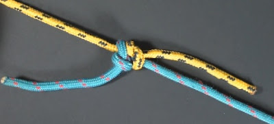 a standard (single) fisherman's knot in yellow and blue paracord