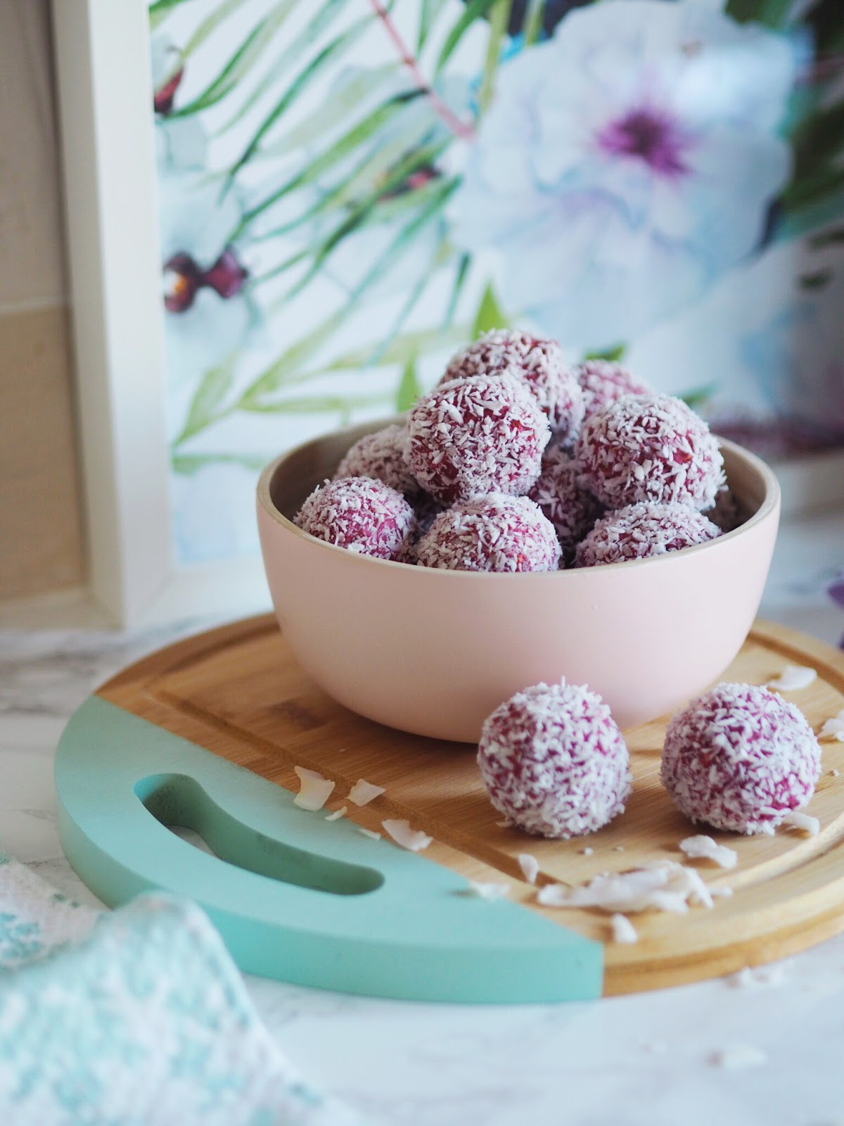 Pink Energy balls on wood board in pink bamboo bowl