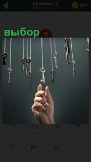На веревочках висят несколько ключей, один из которых выбор рукой