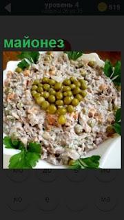 На блюде приготовлен салат оливье, заправленный майонезом и горошком