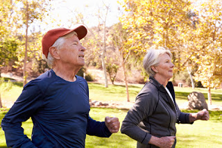 Photo of two seniors jogging in autumn