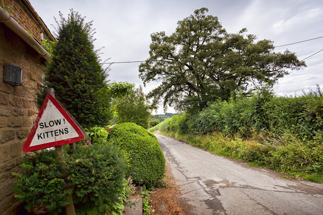 An amusing road sign in Great Tew in the Cotswolds by  Martyn Ferry Photography