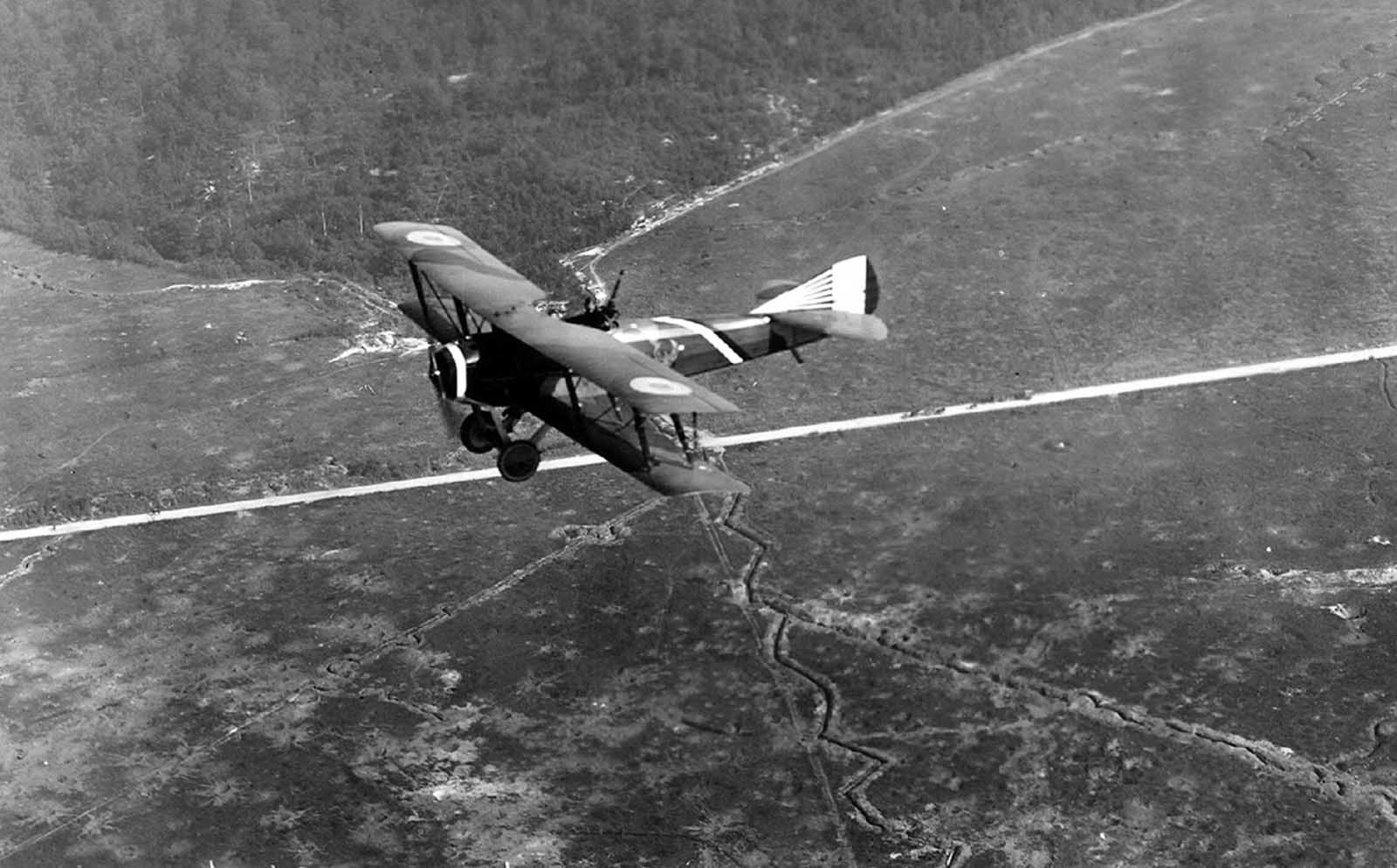 A French SPAD S.XVI two-seat biplane reconnaissance aircraft, flying over Compeign Sector, France ca. 1918. Note the zig-zag patterns of defensive trenches in the fields below.