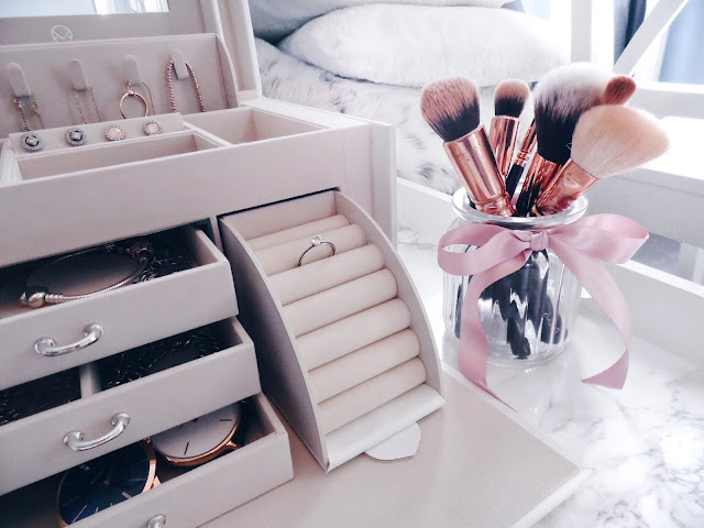 jewellery box next to glass jar of make up brushes