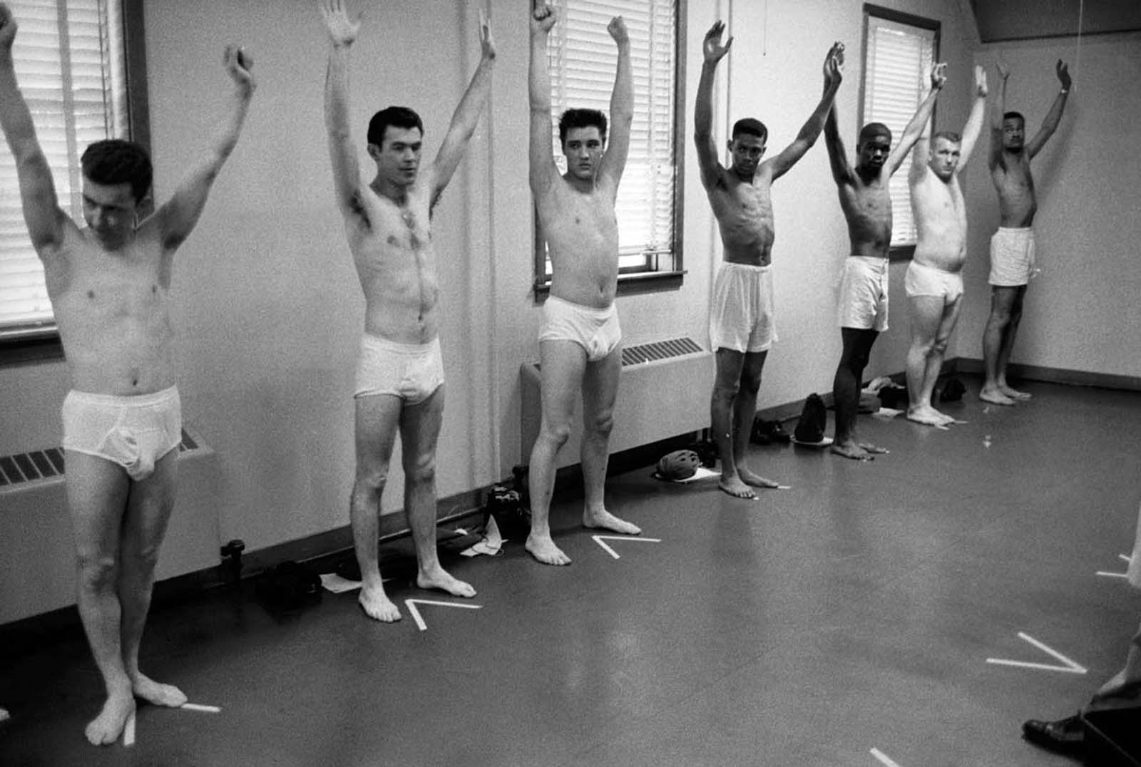 Wearing only underwear, Pvt. Elvis Presley raises his arms along with several other inductees during an inspection at Ft. Chaffee.