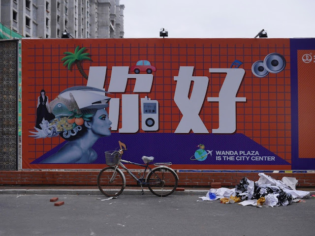 "Wanda Plaza ""你好"" sign on a wall bordering a construction site in Mudanjiang, China"
