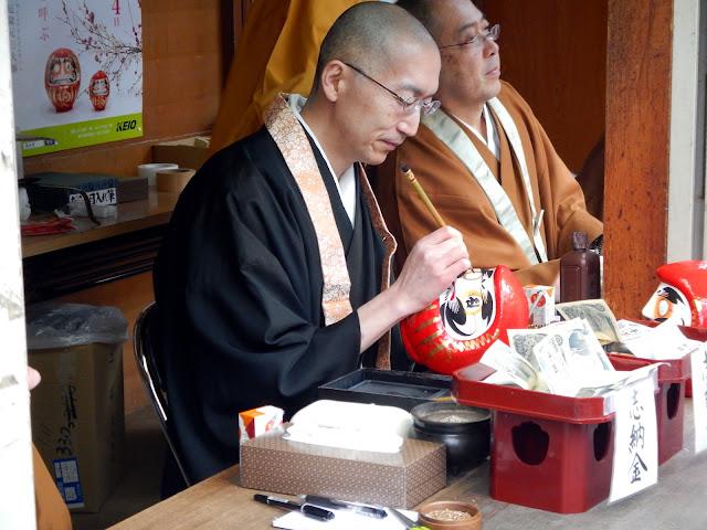 Un monje pintando el segundo ojo de un Daruma