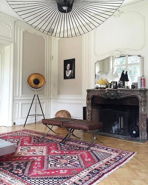 paris living room with parquet floor, marble fire place and vertigo lighting by constance guisset