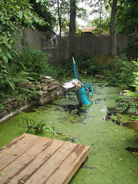 water dragon junk model lurking in the wildlife garden at windmill hill city farm in bristol