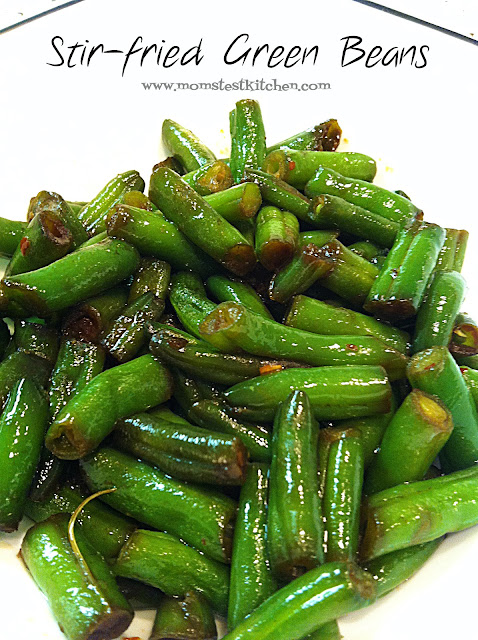 old photo of stir-fry green beans. Beans on a white plate with label