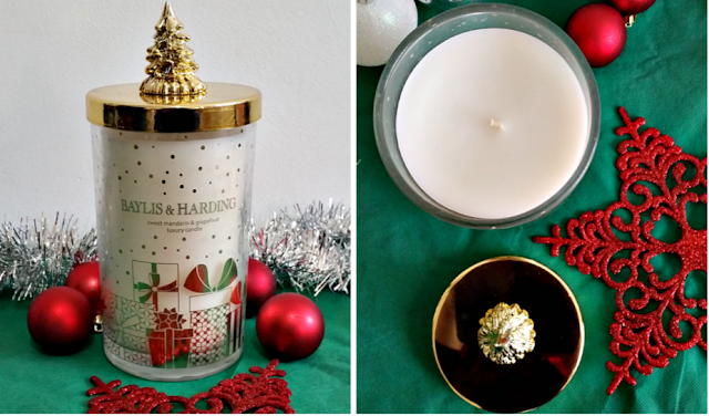 a white candle in a glass jar with a beautiful gold lid with a christmas tree on.