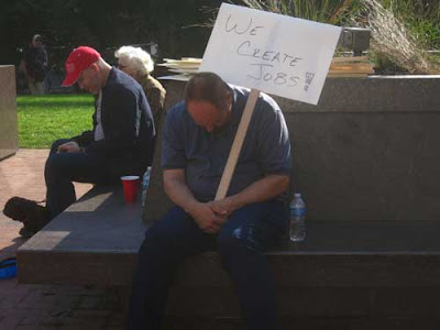 Man sitting, slumped and possibly asleep, holding a sign on his shoulder that says We Create Jobs