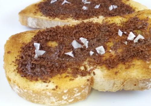 Dos tostadas con chocolate, aceite y sal