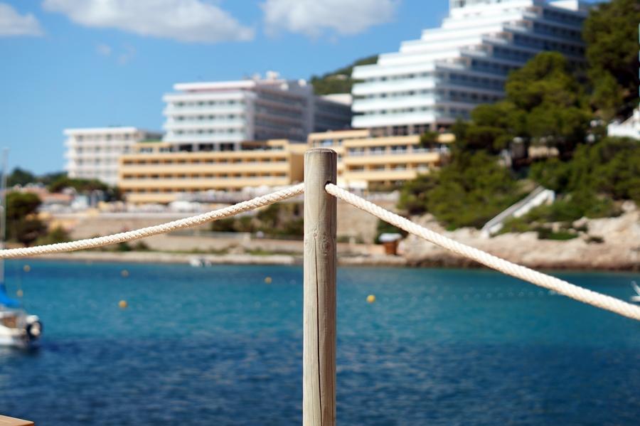 Blog + Fotografie by it's me fim.works - La Isla Blanca Ibiza, Cala Llonga, Holzpfhal, Hotels im Hintergrund