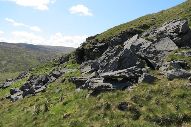 Exposed rocks near the top of Catlow Hill with a view to moorland in the background.
