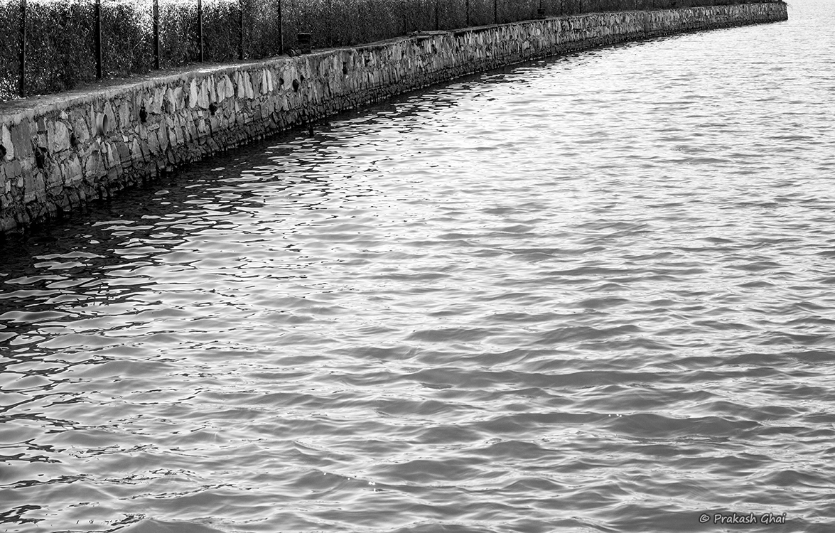 A Black and white Minimalist Photo of Sea dock used as a curve & still water as negative space.