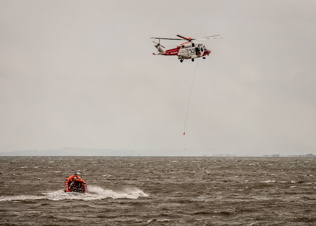 Photo of the Coastguard helicopter lowering the winch line