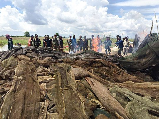 Authorities burn a pile of fishing nets in Kandal province earlier this week after they were seized for illegal use. Photo supplied