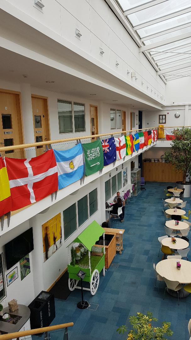 Cafeteria at a UK tech company displaying flags from World Cup nations, June 2018