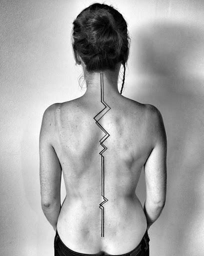 Um zigue-zague linha preta corre o comprimento do utente vertebral, essa tatuagem.
