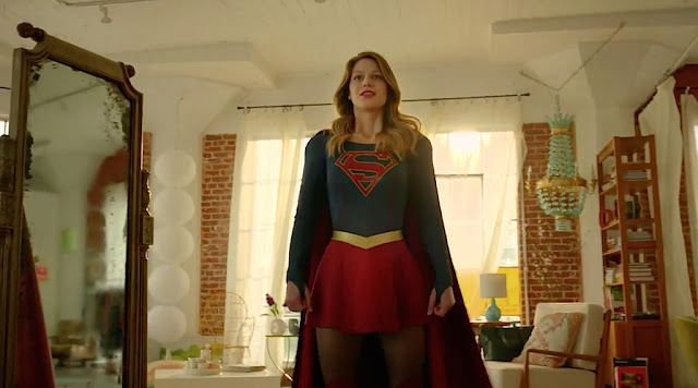 A screenshot of Supergirl, a young, blonde white woman in a dress with a blue bodice, short red skirt, and red cape, standing in her apartment. The place is a converted warehouse with red brick walls and floor to ceiling windows made up of many smaller leaded panes and covered by gauzy white drapes.
