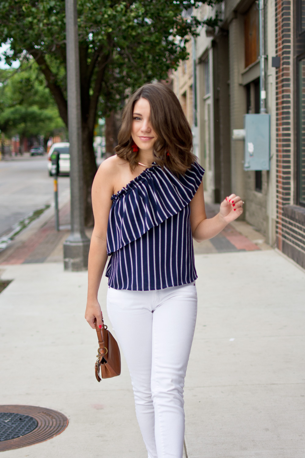 A preppy 4th of July outfit idea featuring a navy pinstripe one shoulder ruffle top, white skinny jeans, and a pair of red statement earrings