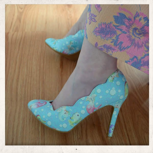 feet wearing blue mermaid printed court shoes with hem of floral skirt in view
