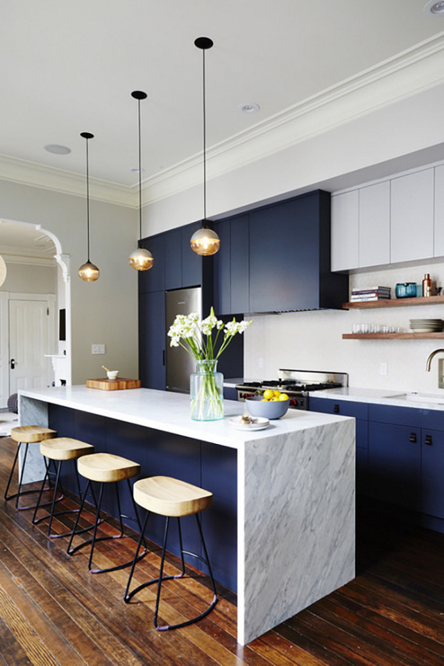 Modern and sleek kitchen with navy blue cabinets and #waterfallisland