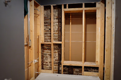 wood framing shower tub surround exposed brick exterior