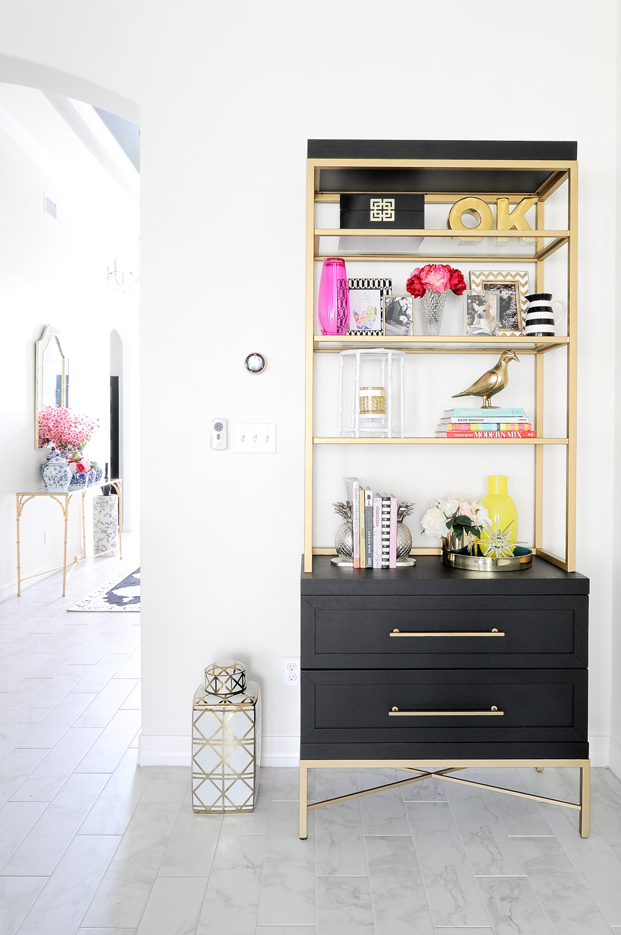 Black and gold etagere or bookcase decorated and styled with spring colors and floral accents.