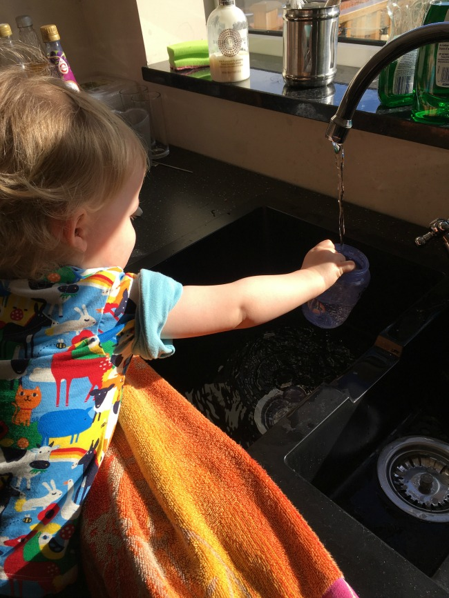 toddler at sink playing with running water