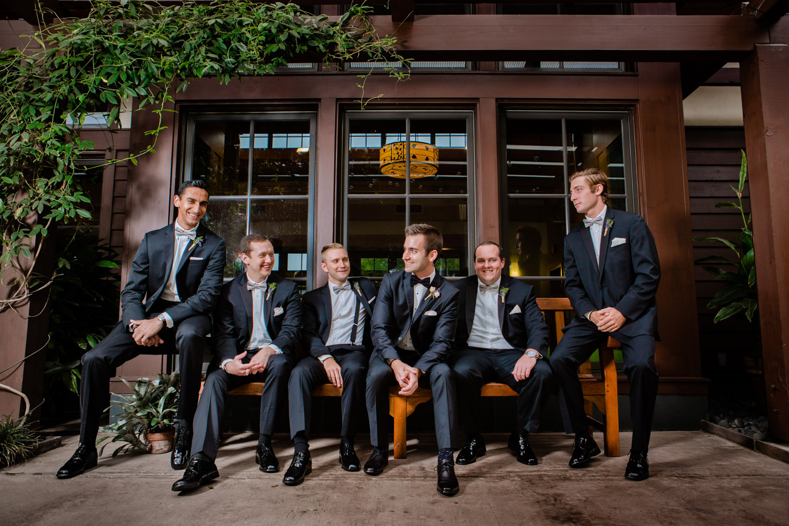 the groomsmen sit together looking poised