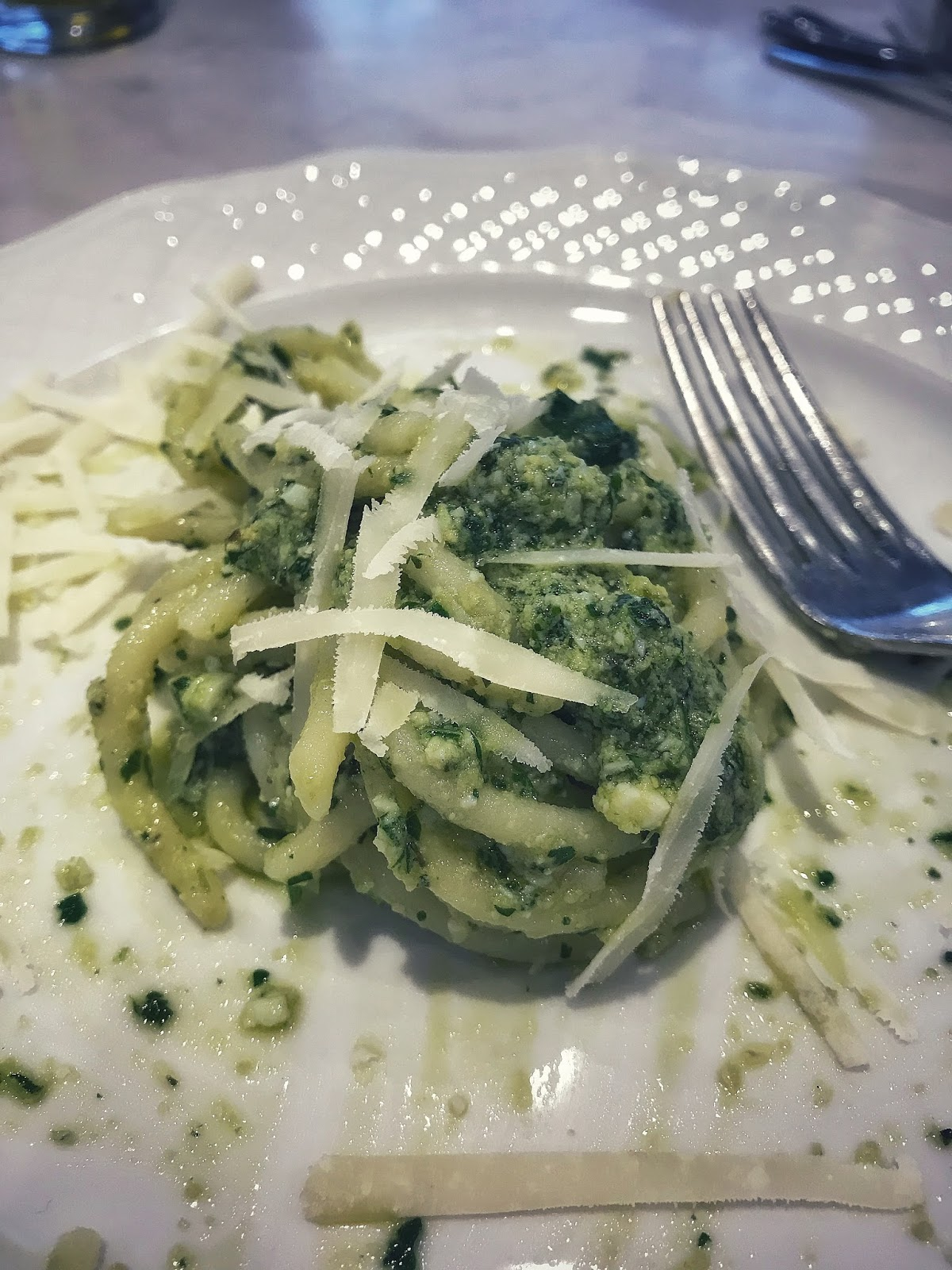 Italian Pici Spaghetti topped with pesto sauce and parmesan cheese