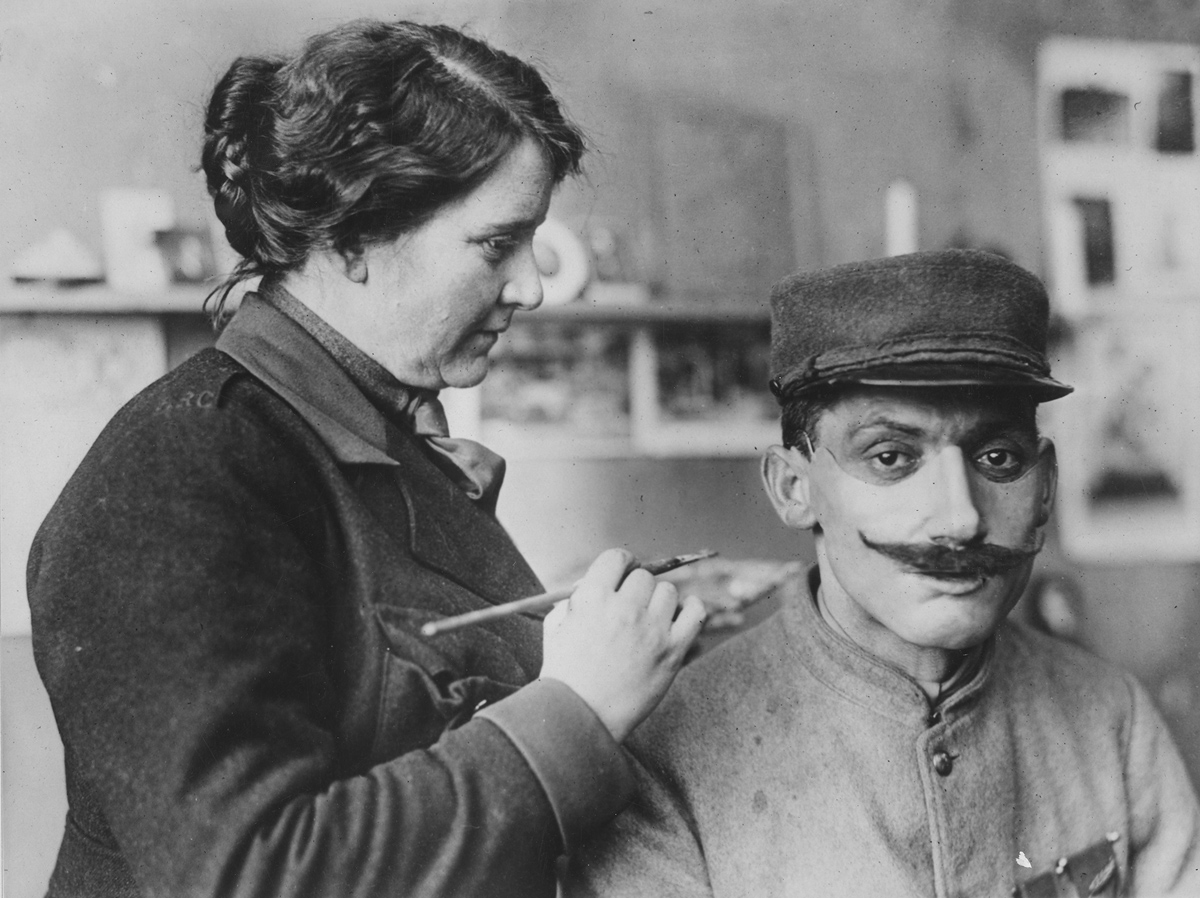 Masks made for men with disfigured faces from war wounds. Original caption: Mrs. Ladd coloring one of the masks after adjusting on a wounded Poilu's face.