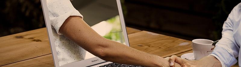 Una persona delante de un portátil da la mano a un brazo que sale de la pantalla del portátil.