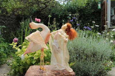 Birth Dance sculpture by Corina Duyn. A bird and a young girl, of same size, pictured in a summer garden