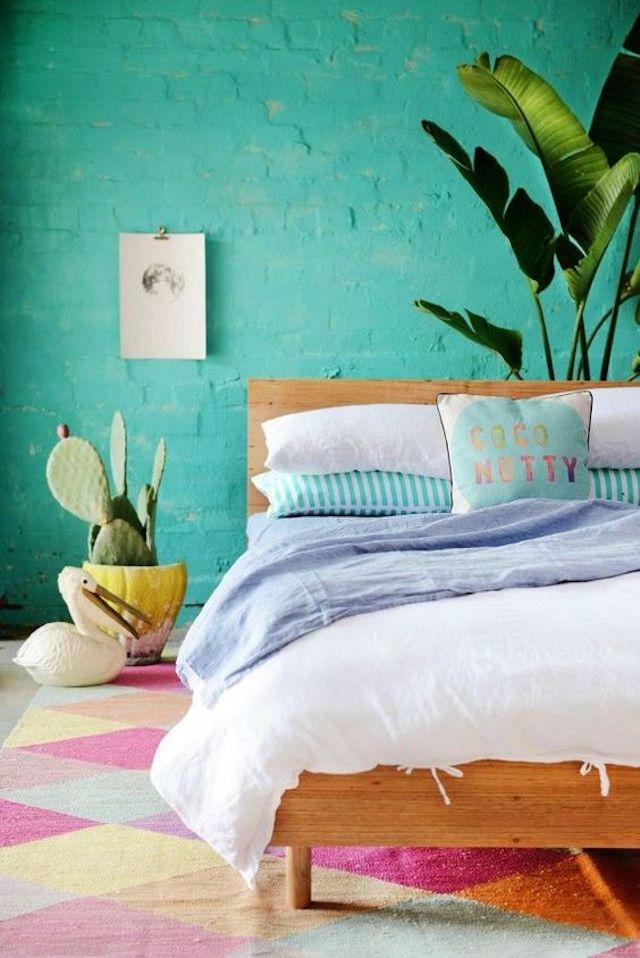 Dormitorio con pared de ladrillo pintada de verde claro. Decorado con platanera y detalles tropicales.