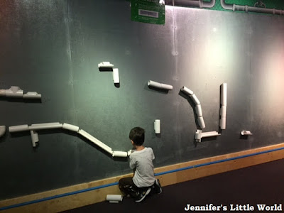 Child playing with pipes along the wall