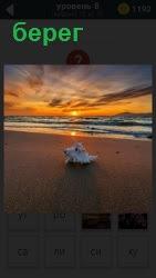 Пустынный пляж на берегу моря в свете великолепного заката, который отражается в воде