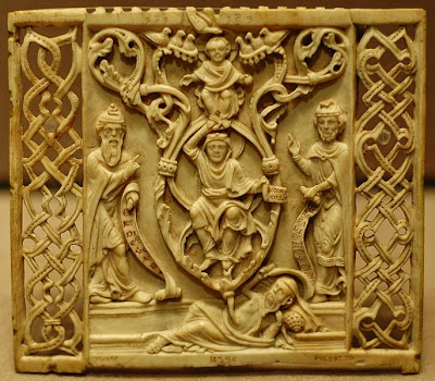 A rectangular back of an ivory comb from Bavaria, from about 1200 CE, showing Jesse lying with the Tree emerging from his navel. Above Jesse is seated Mother Mary, with the infant Jesus on top surrounded by seven doves.