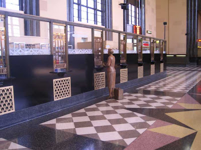 Ticket windows with metal grates. A sculpted woman figure stands at one window
