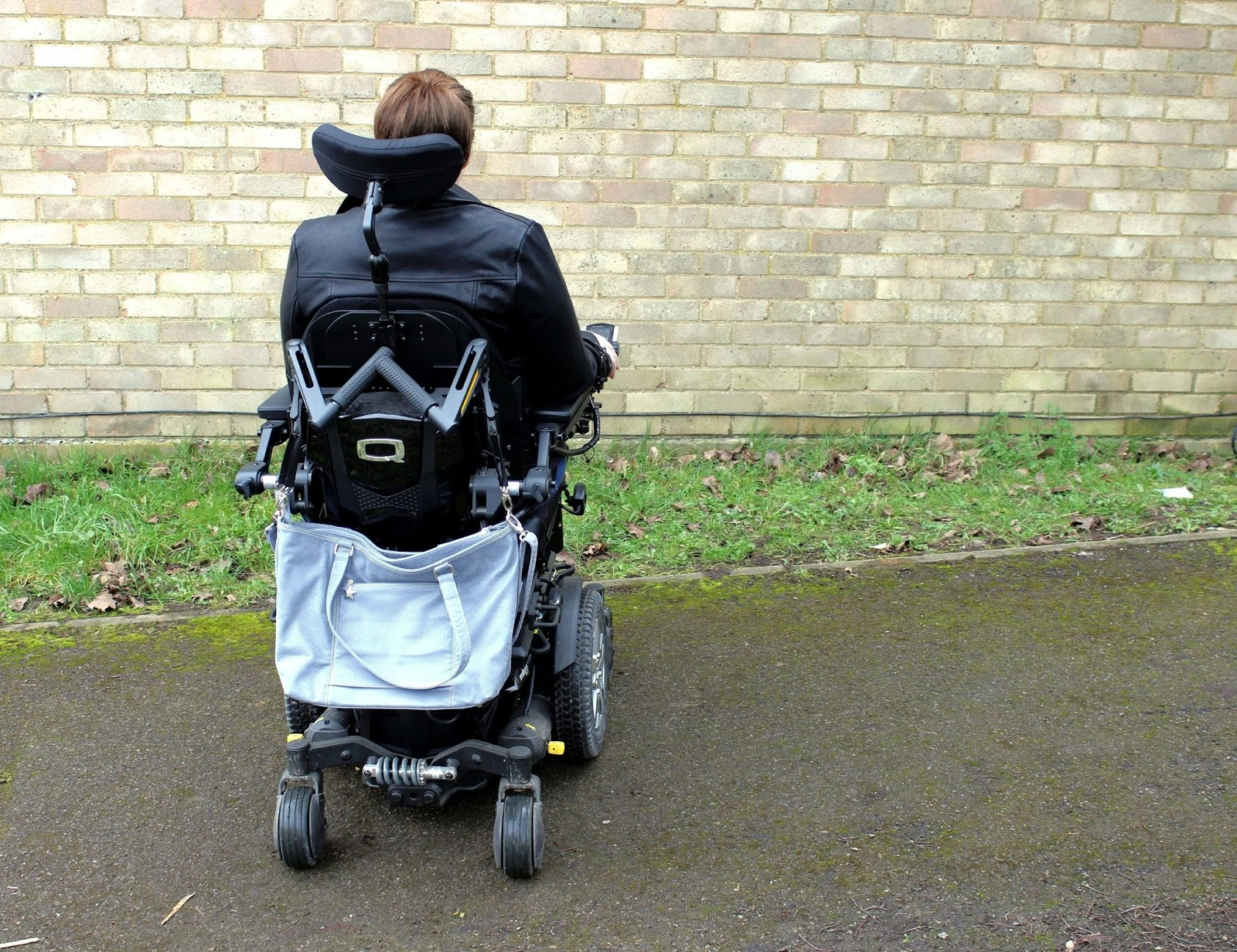 Shona is sitting in her powerchair, the image has been taken from behind, there is a large grey handbag on the back of her powerchair. Background is a brick wall.