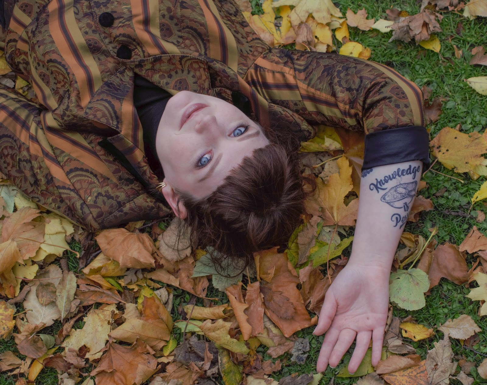 Autumn inspiration  photo with blogger Lauren Aitchison lying in pile of leaves