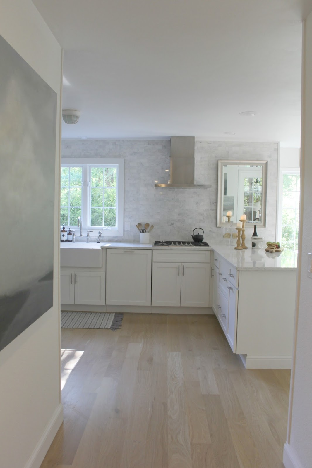 Serene white kitchen with white oak hardwood flooring. Shaker kitchen cabinets, Viatera quartz countertop (Minuet). Carrara subway tile taken to the ceiling. Modern range hood. Wall color is Benjamin Moore WHITE. #hellolovelystudio #whitekitchen #serene #whiteoak #benjaminmoorewhite #viateraquartz #minuet